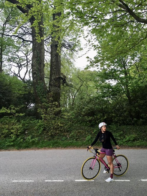 Woman on a bike wearing a helmet and cycling shorts. She's on an empty country road with a forest in the background.