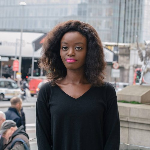 Young black woman stands outside. Behind her is a high rise glass building, and a busy London street.