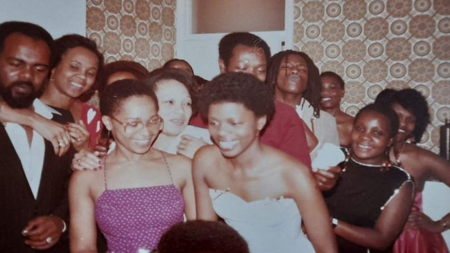 A group of young black people crammed into a living room.
