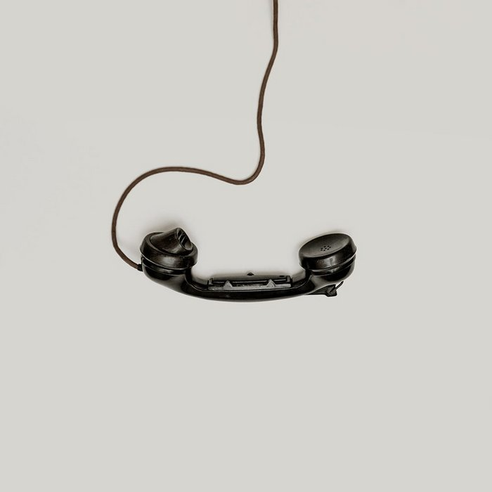 Black corded rotary phone receiver on a beige background.