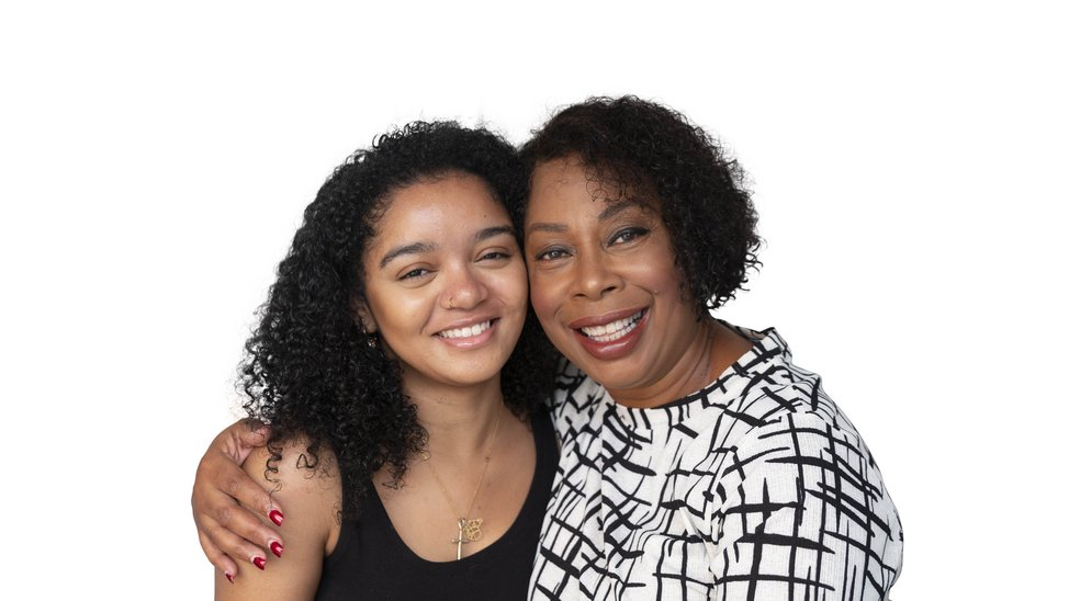 Young mixed race black woman is hugged by an older black woman.