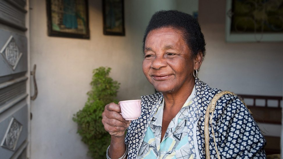 Older black woman holding a small teacup and smiling into the distance.