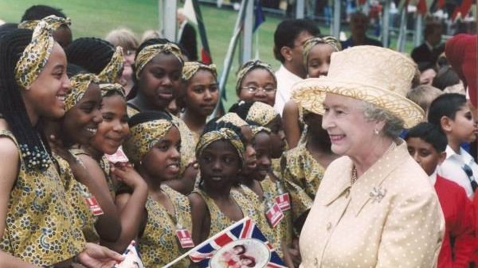 The Queen in a lemon yellow skirt suit with matching hat, smiling at a group of black children in matching print clothing waving Union Jacks.