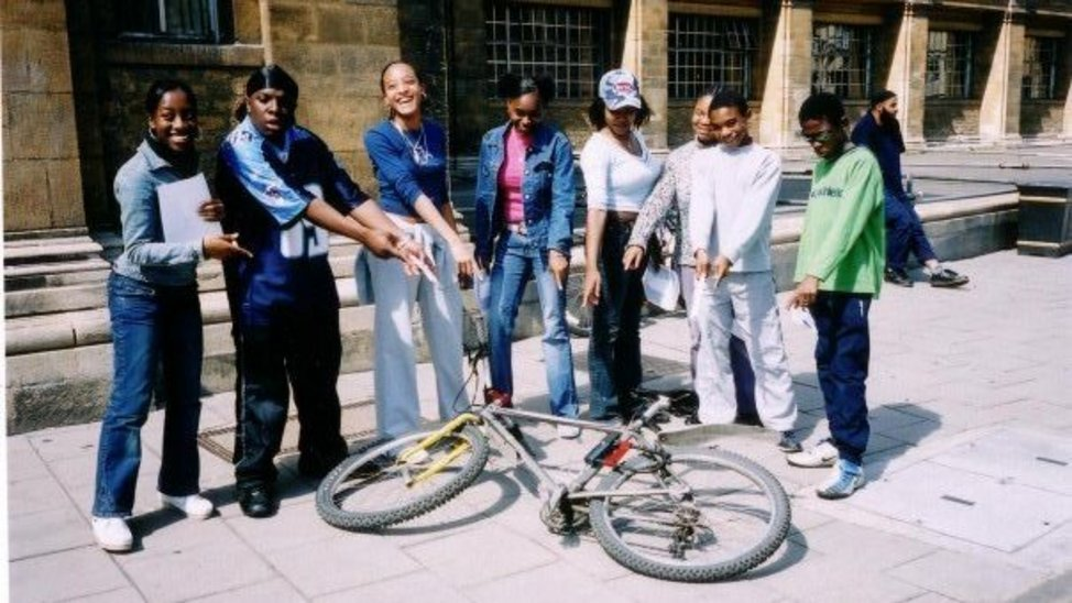 Group of eight young people stand in a semi-circle pointing at a bike that is laying on the floor.